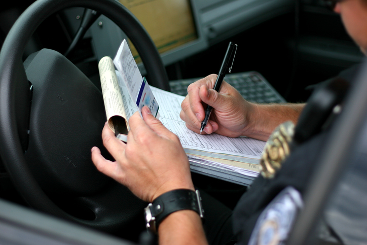 Police officer writing ticket for someone needing a criminal defense lawyer